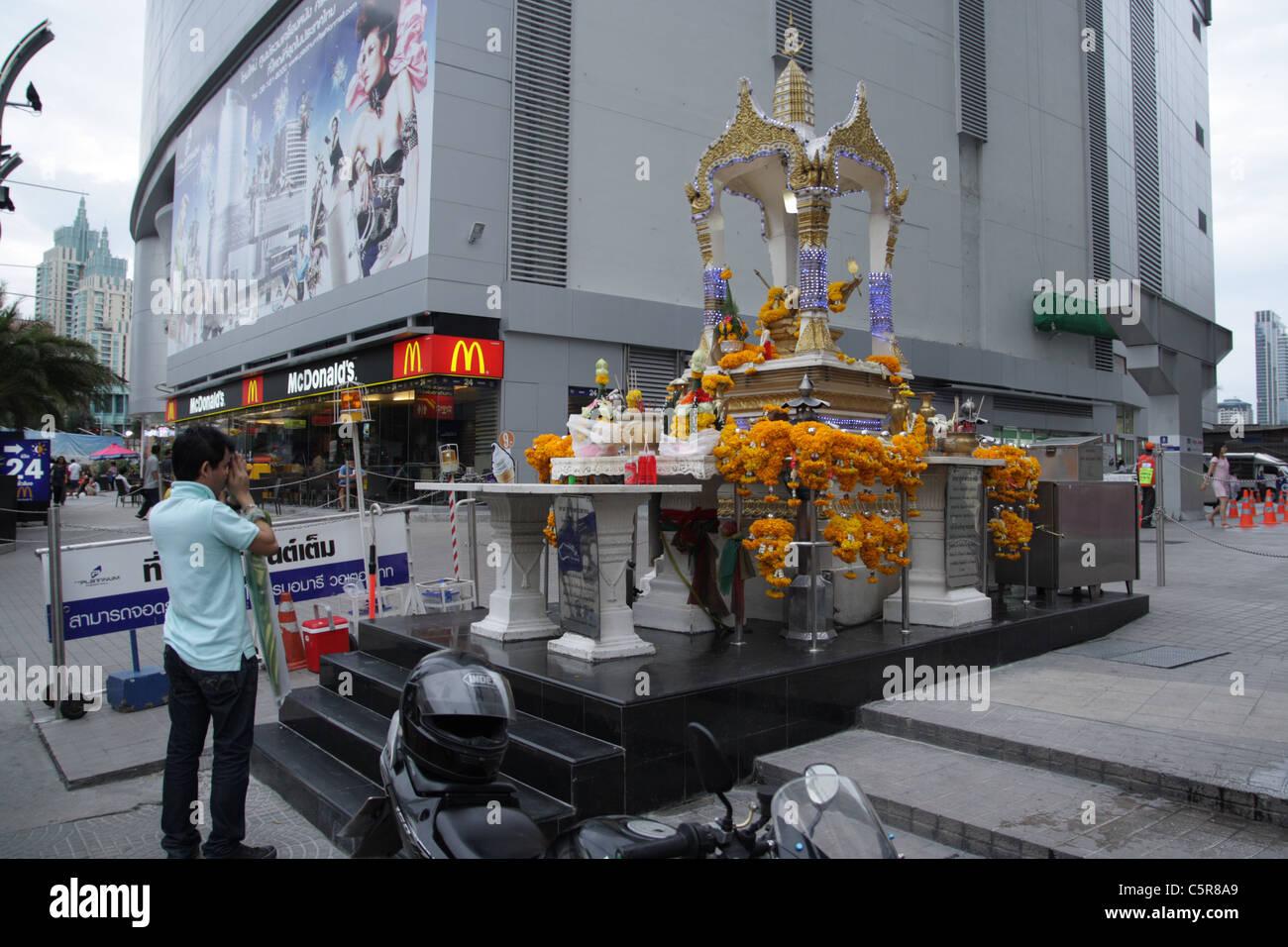 A man preying at spirit house shrine near shopping mall - Stock Image