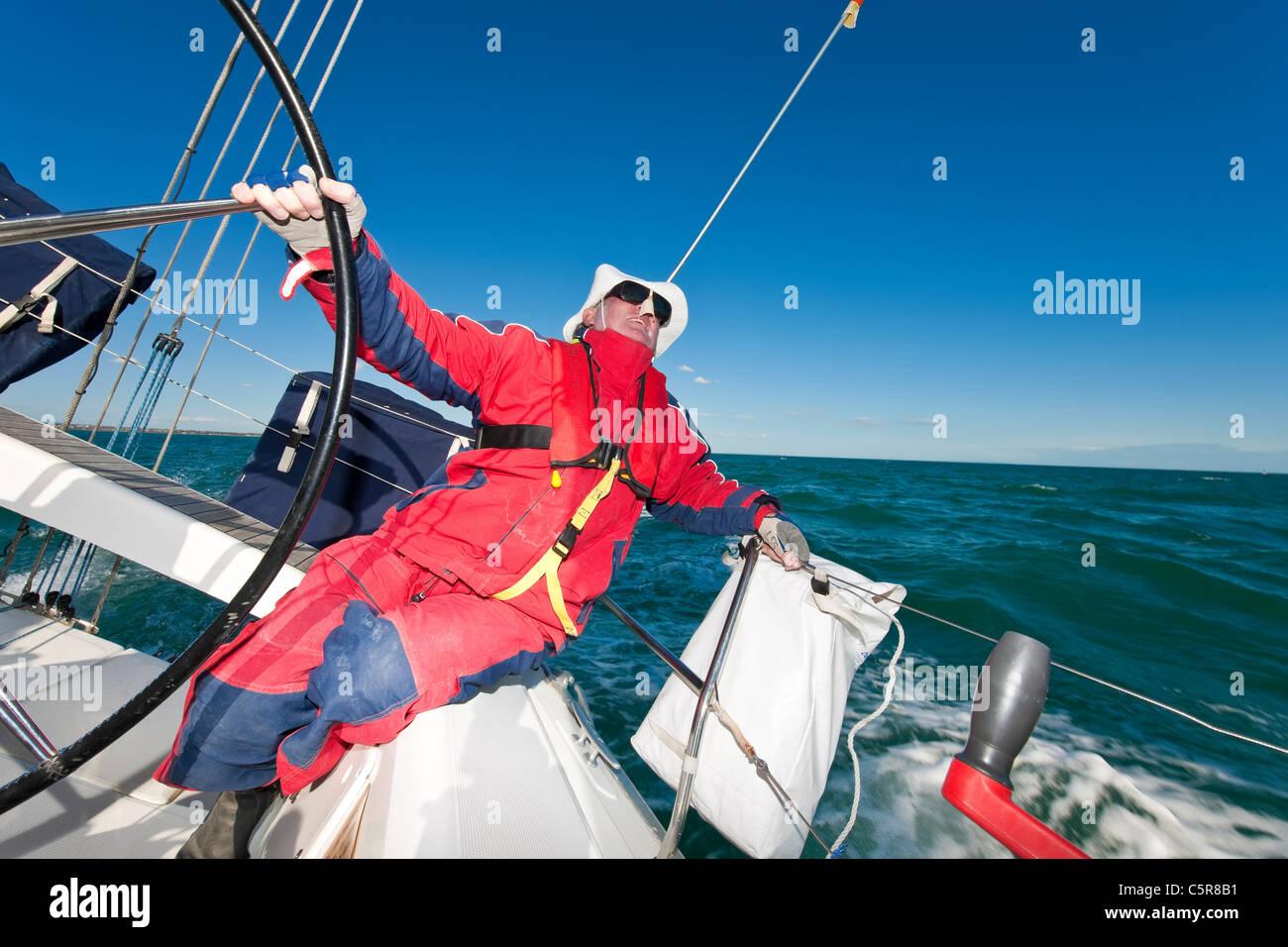 Senior Citizen captain at the wheel of ocean going yacht. - Stock Image