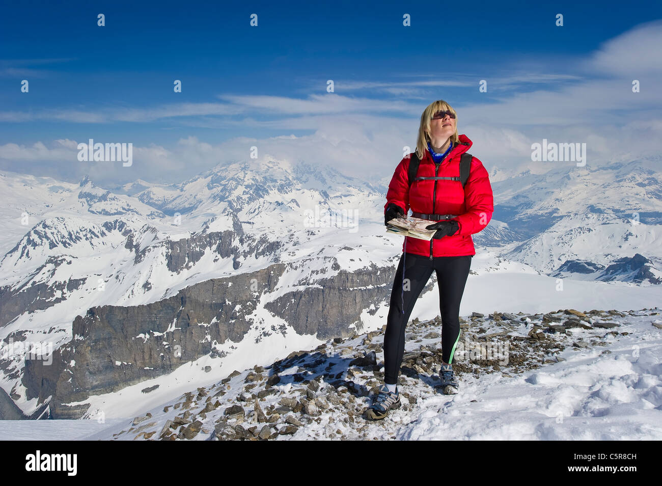 A women in high snowy mountains using a map and compass for orienteering. - Stock Image