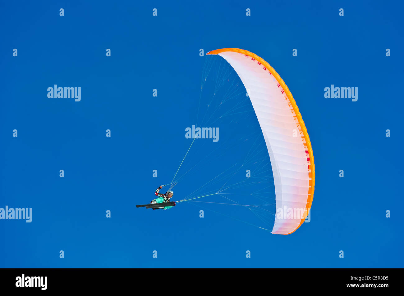 A Paraglider pilot smiles as makes makes a fast banked turn. - Stock Image