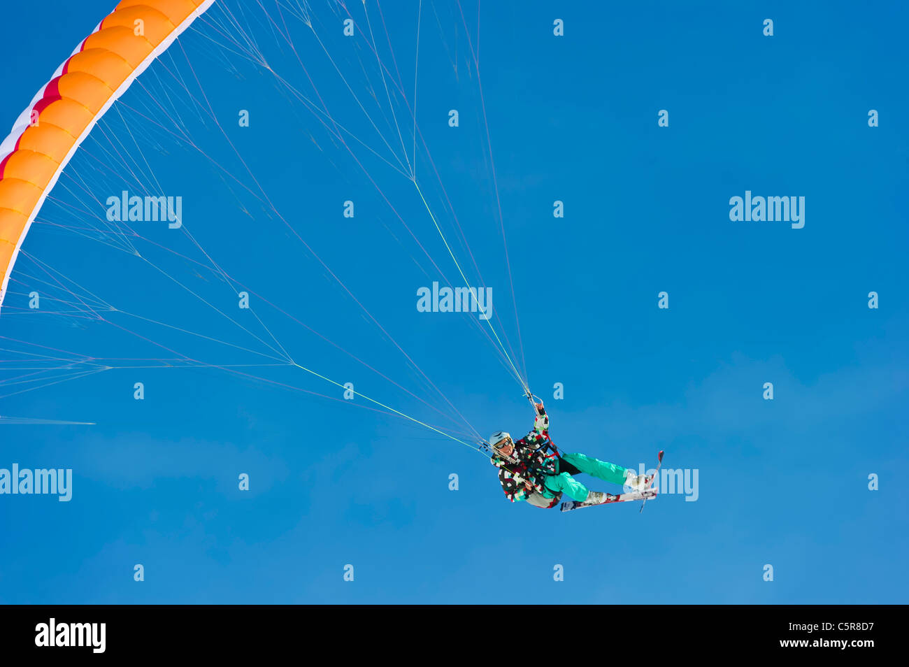 A female Paraglider in a high powered turn smiles. - Stock Image