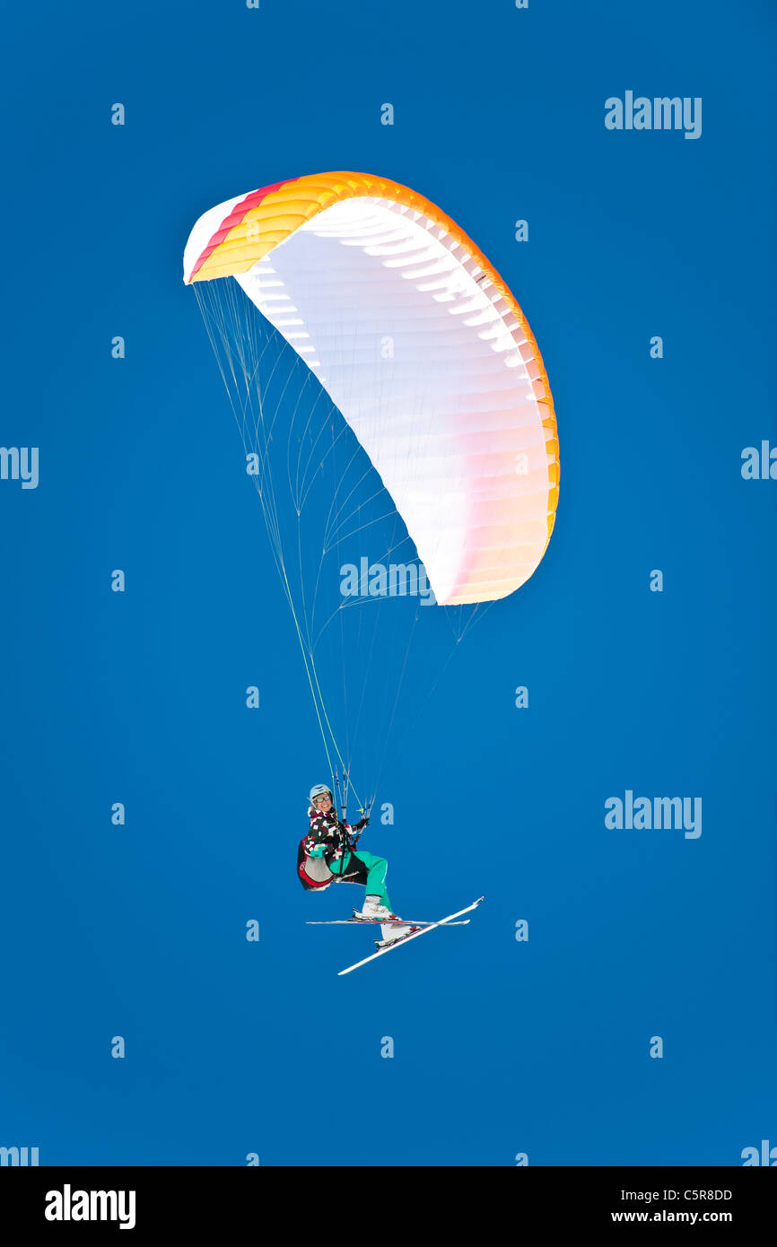 A female Paraglider pilot smiles as she fly's her wing. - Stock Image