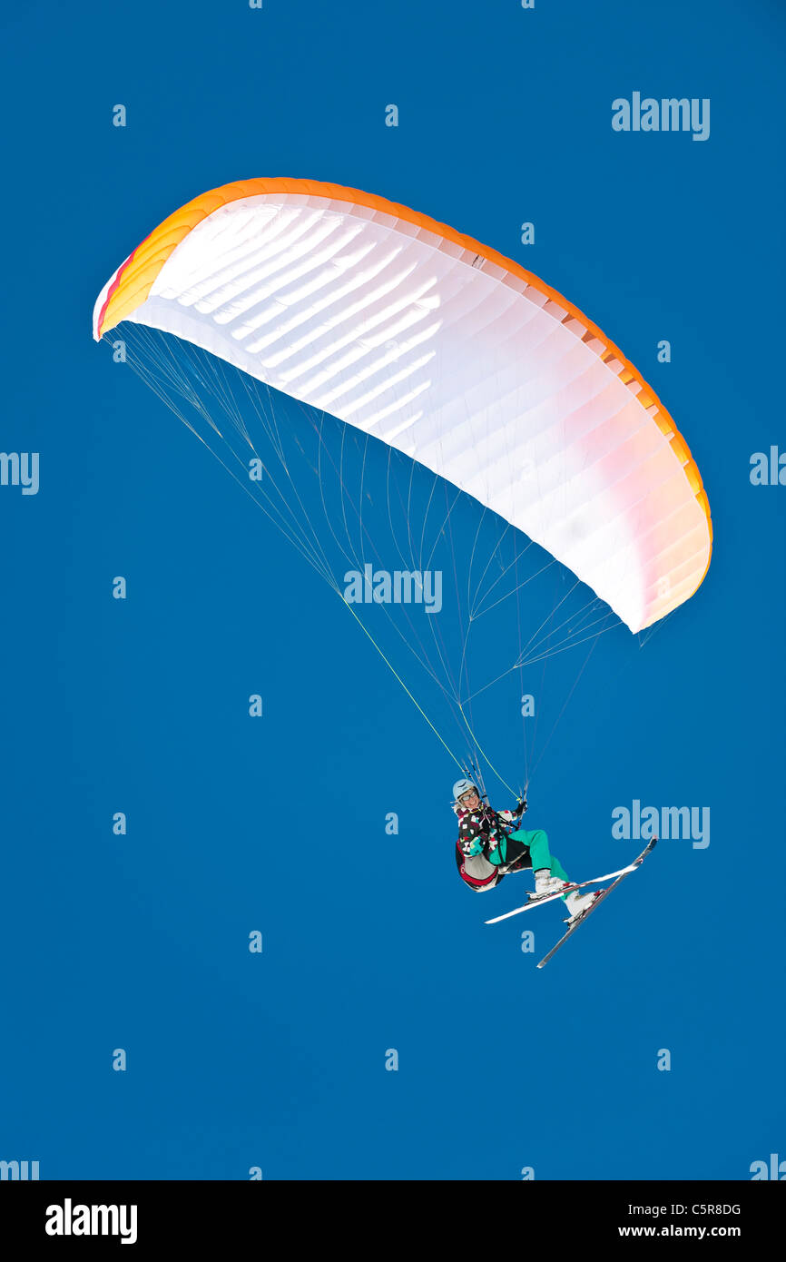 A Paragliding winter sports enthusiast smiles whilst flying. - Stock Image