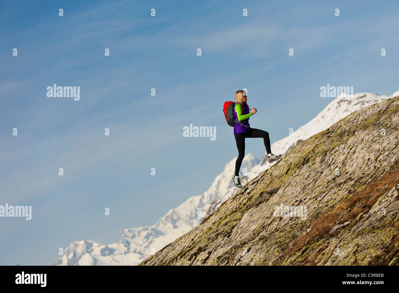 A runner runs up a steep mountain rock face at high altitude. - Stock Image