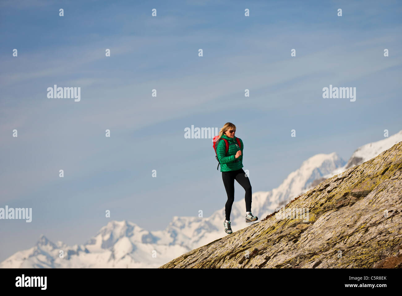 A runner runs over a rocky mountain. - Stock Image