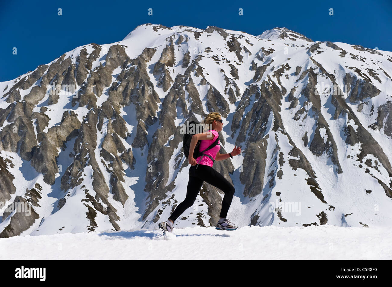 Jogger runs past a stunning snowy mountain. - Stock Image