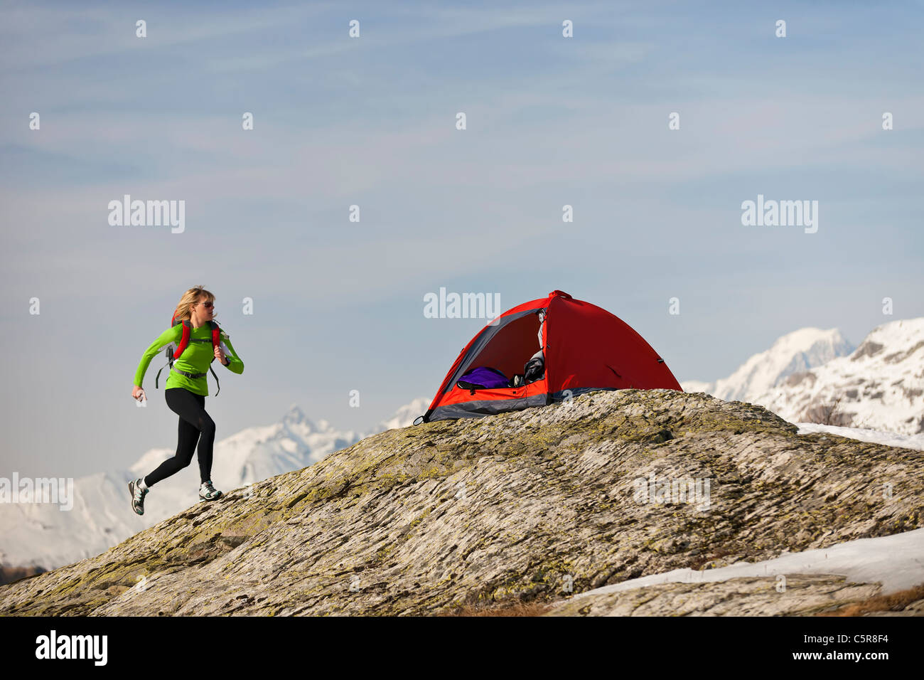 A woman runs back to her tent in high altitude mountains. - Stock Image