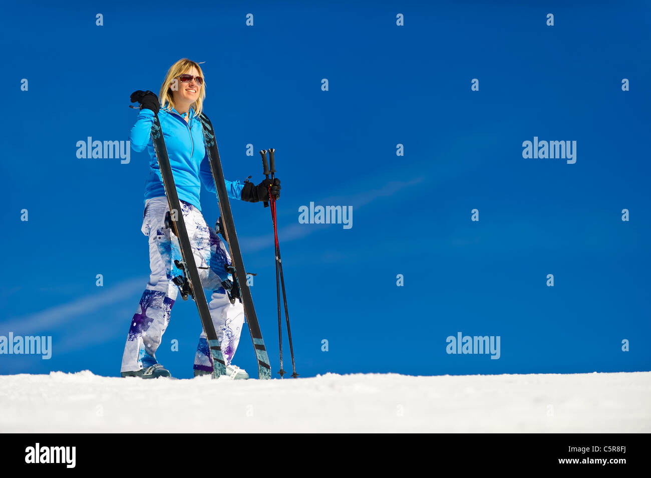 A woman enjoying herself stands on the ski slope with her skis. - Stock Image