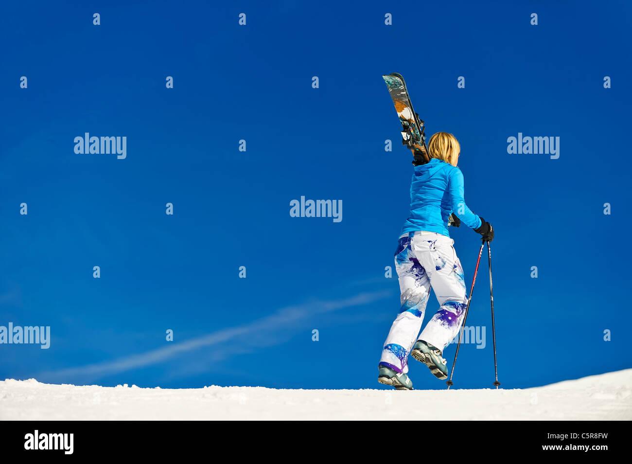 A female skier walking along the piste. - Stock Image