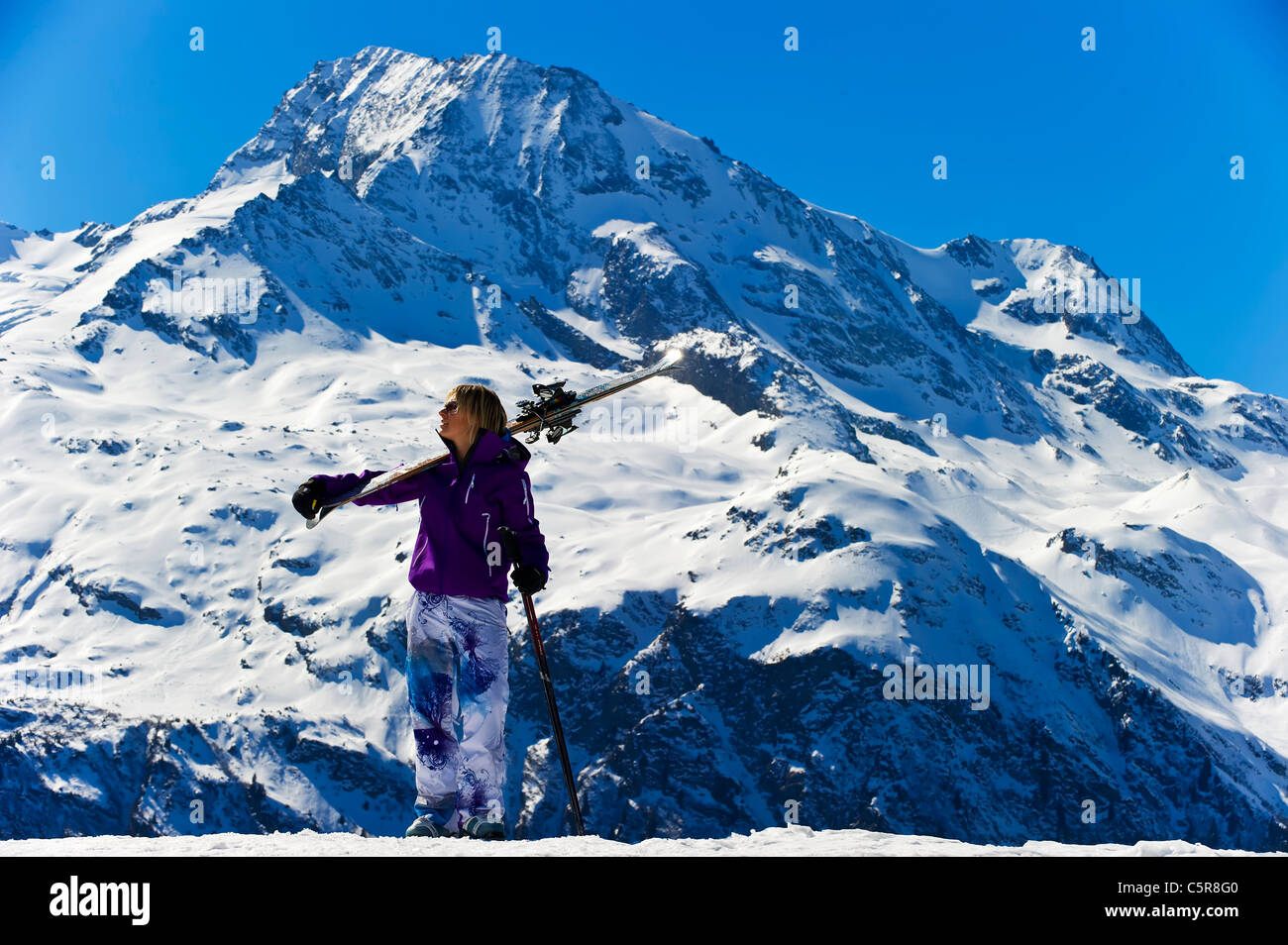 A skier looks out of the mountains and glaciers. - Stock Image