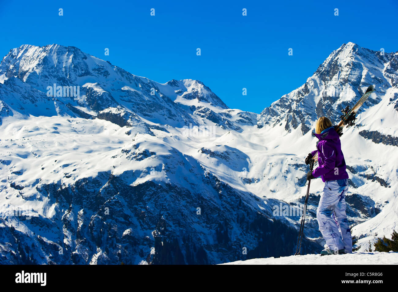A skier looks out over a stunning winter snowy mountains. Stock Photo