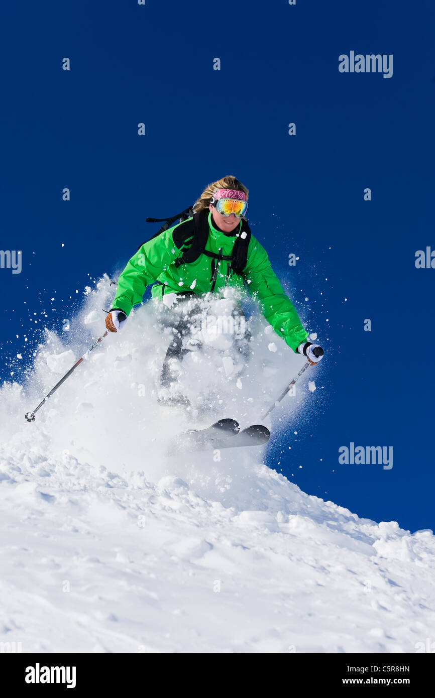 A female skier skis fast through the spring snow. - Stock Image