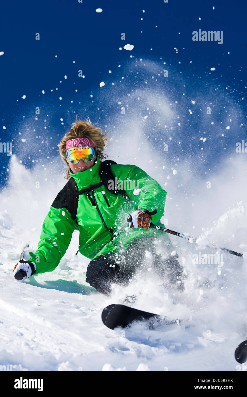 A female skier smiles as she skis hard through the exploding powder snow. - Stock Image
