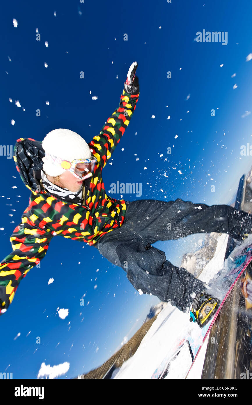 A Snowboarder balancing on a rail in a snow park. - Stock Image
