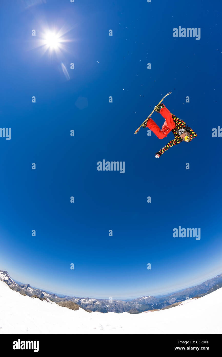 A Snowboarder jumping high into a blue sunny sky. - Stock Image