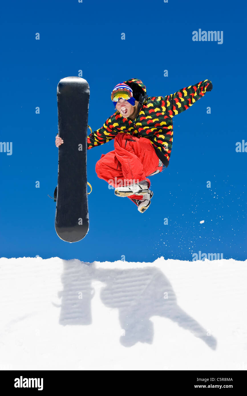 A snowboarder leaps from the side of a half pipe in celebration. - Stock Image