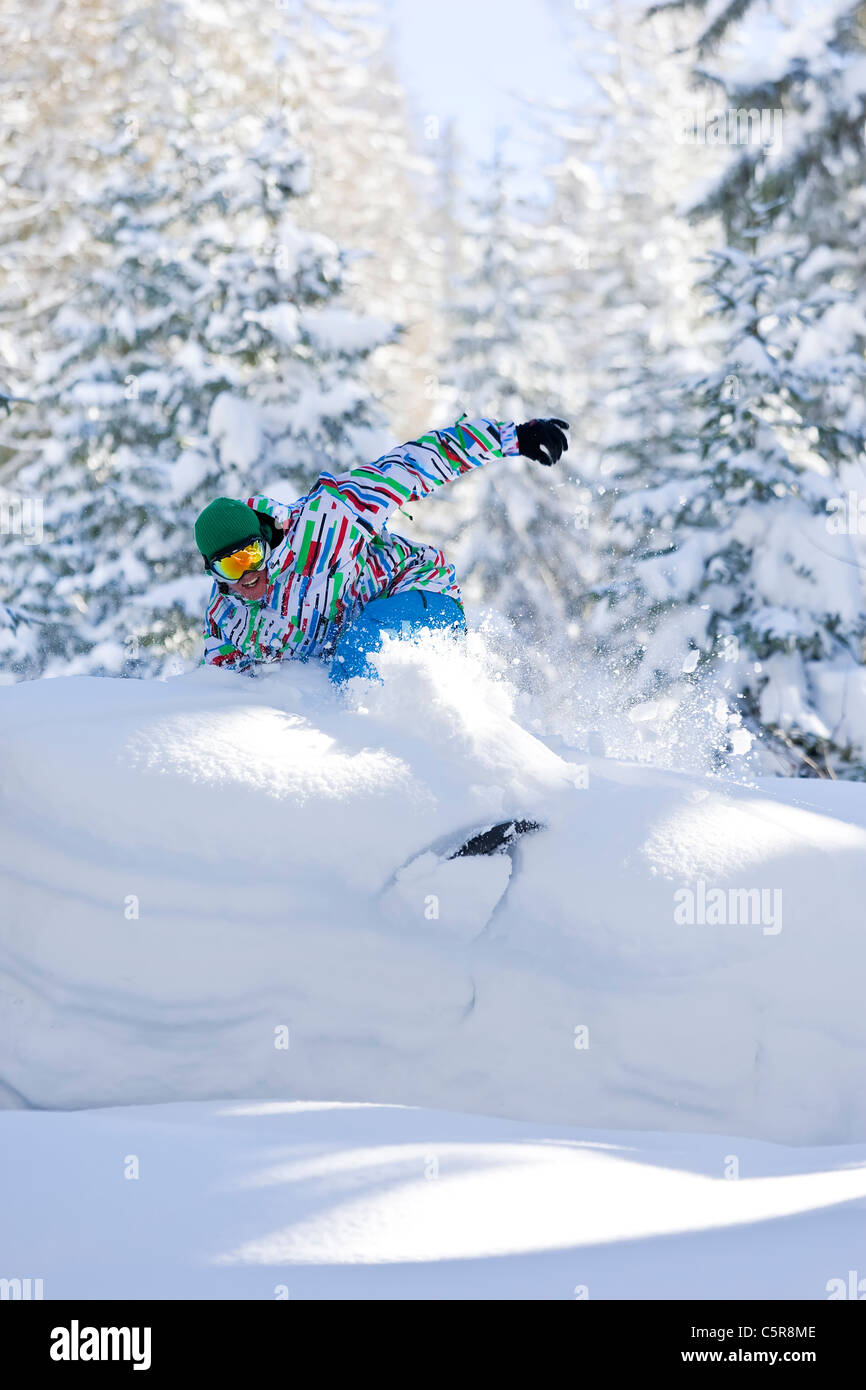 A snowboarder rides deep fresh powder snow through a forest. - Stock Image