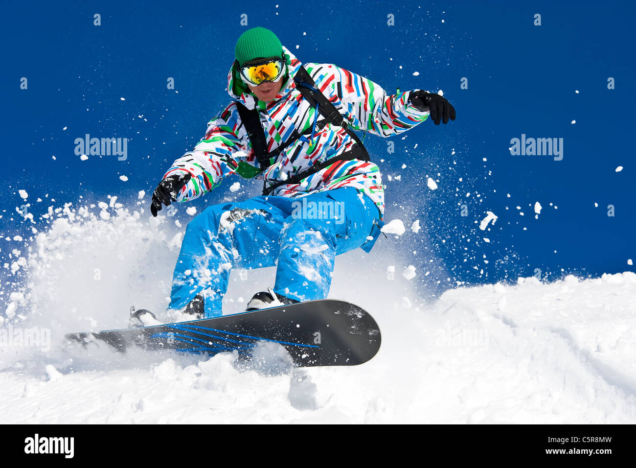 A snowboarder riding hard through off piste snow. - Stock Image