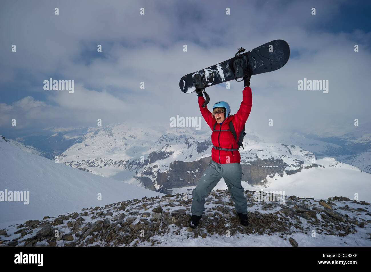 A snowboarder celebrates being on the top of snow covered mountains. - Stock Image