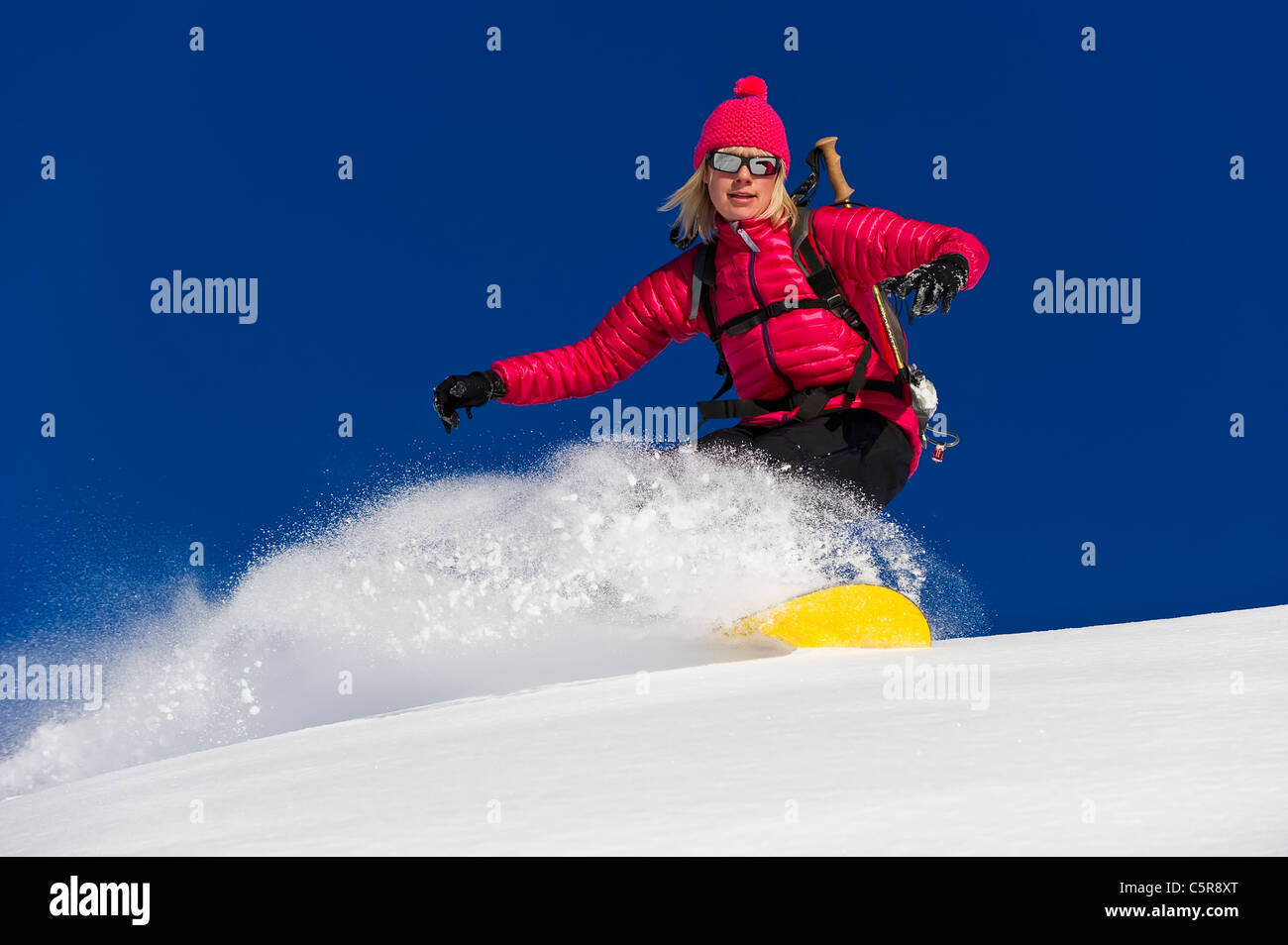 A snowboarder rides deep fresh powder snow at speed. - Stock Image