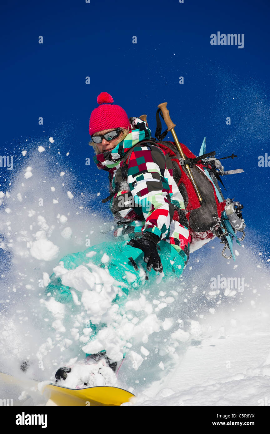 A snowboarder explodes through fresh powder snow. - Stock Image