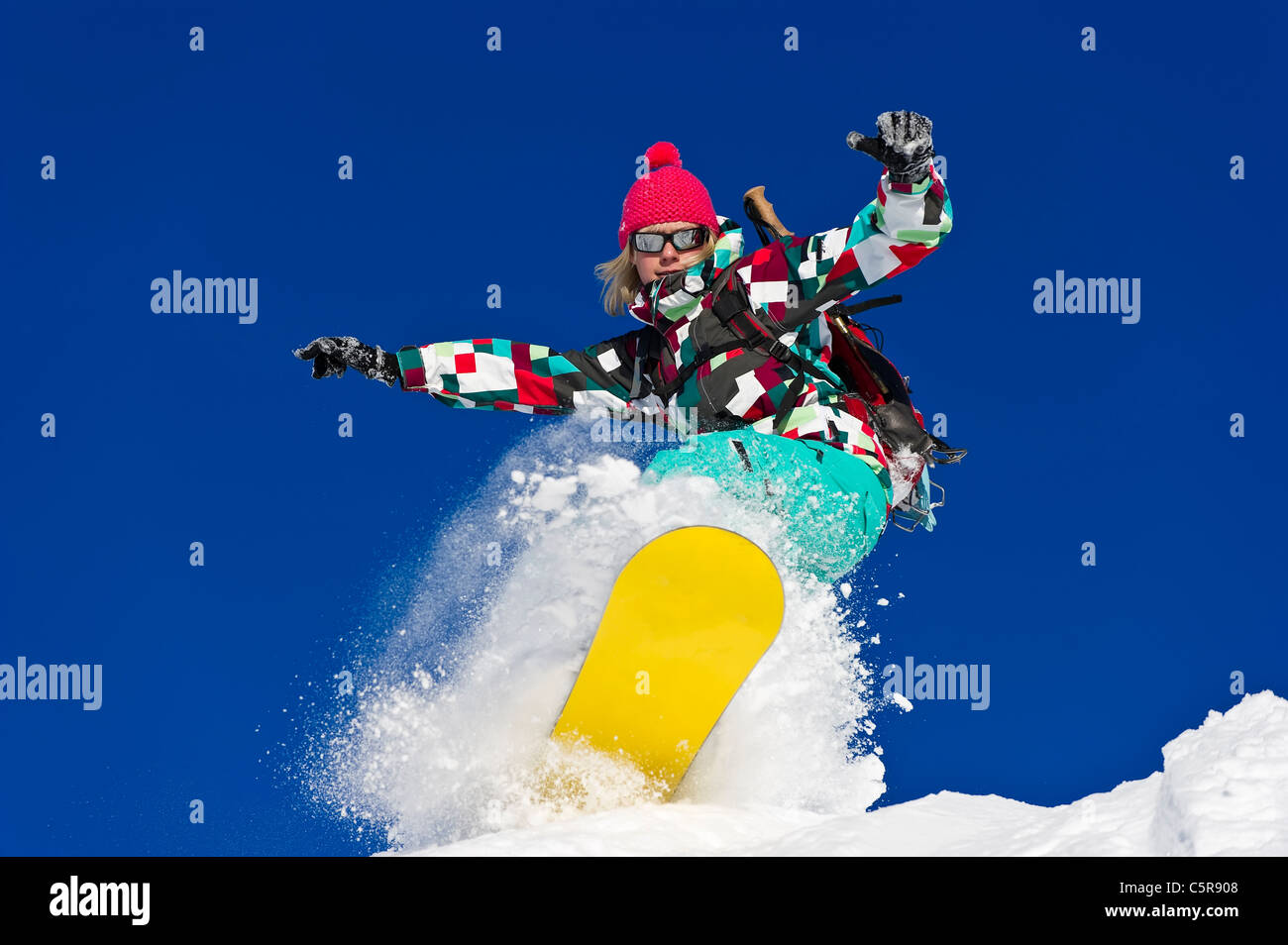 A female snowboarder riding hard through deep fresh powder snow. - Stock Image
