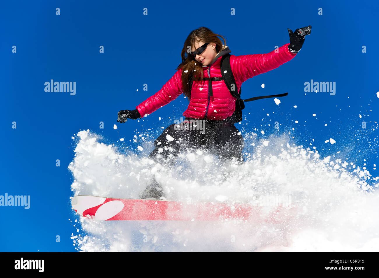 A Snowboarder riding fresh powder snow. - Stock Image