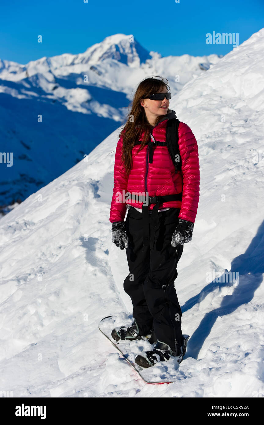 A happy snowboarder takes a look at the mountain scenery. - Stock Image