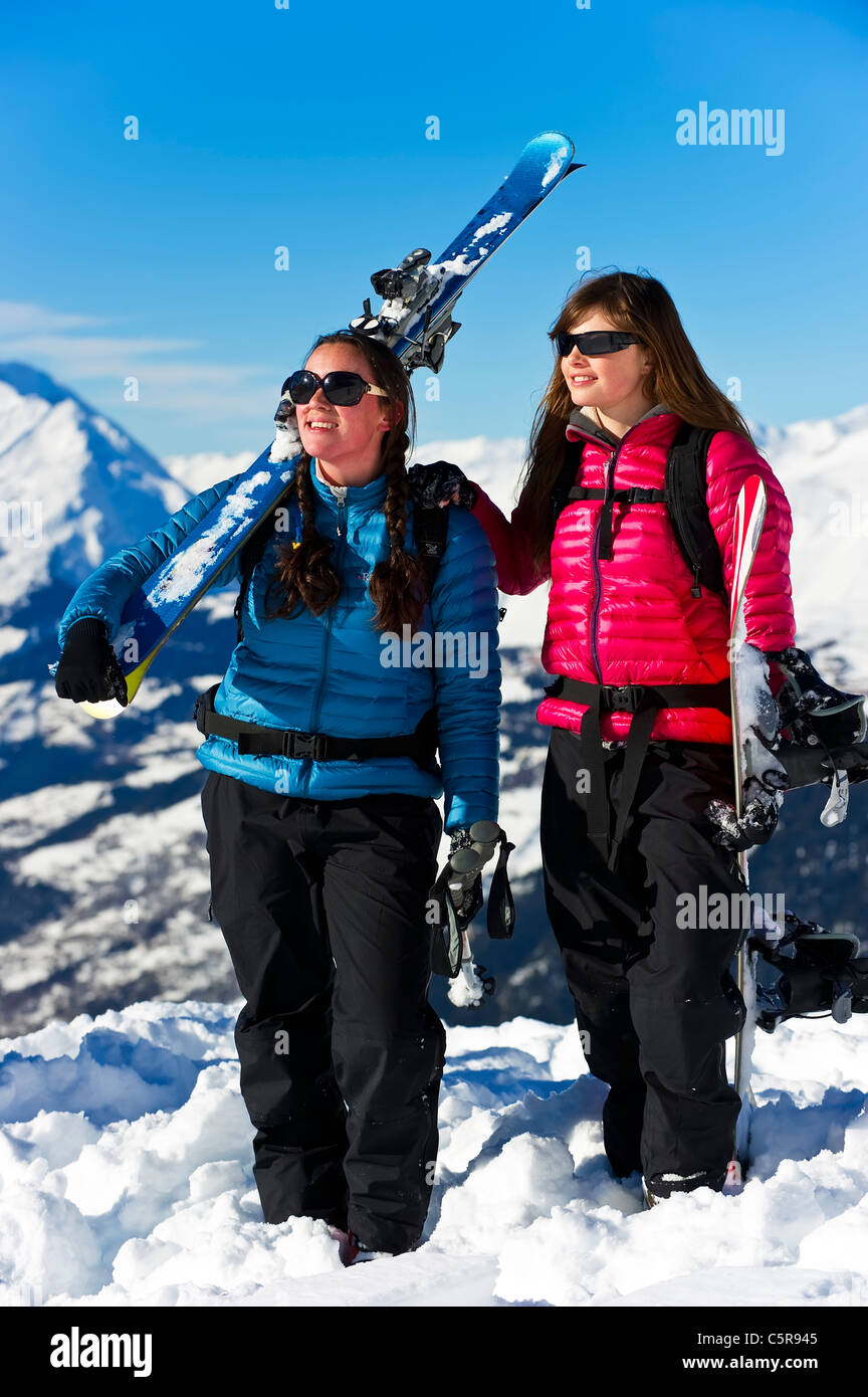 A skier and snowboarder having fun in the snowy mountains. - Stock Image