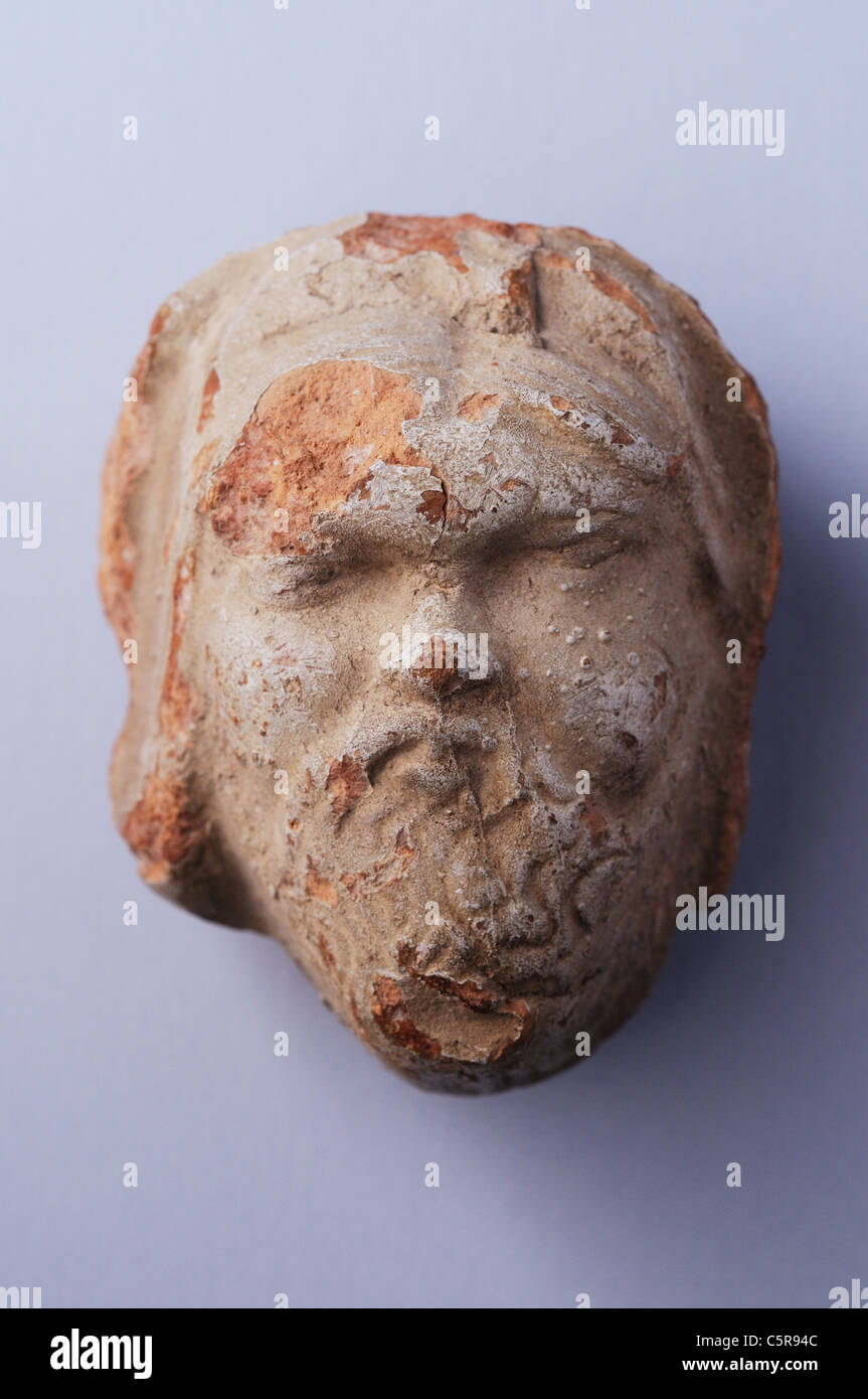 Terracotta antefixes representing a bearded head with clear slip . Roman period in Complutum . SPAIN - Stock Image