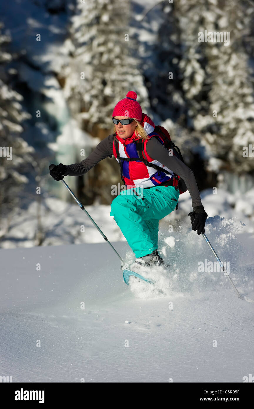 A women running through deep powders snow in snow shoes. - Stock Image