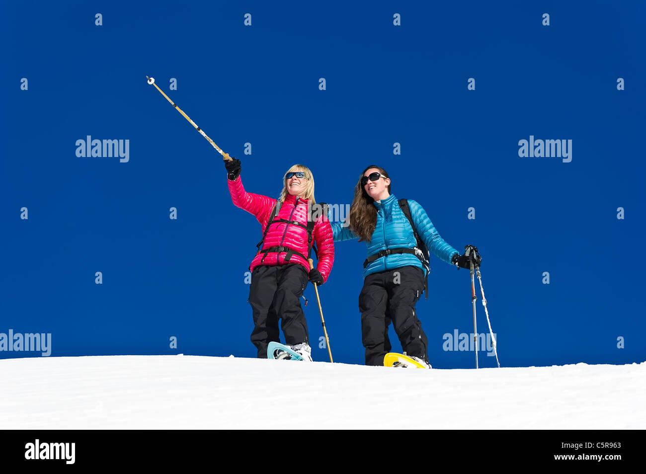 Two friends having fun snowshoeing - Stock Image