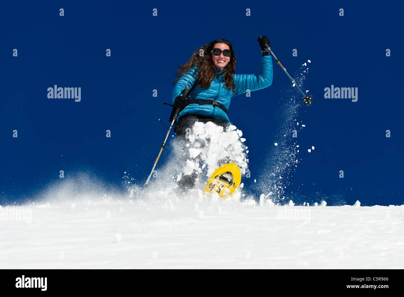A woman having fun snowshoeing down a deep fresh snow field. - Stock Image