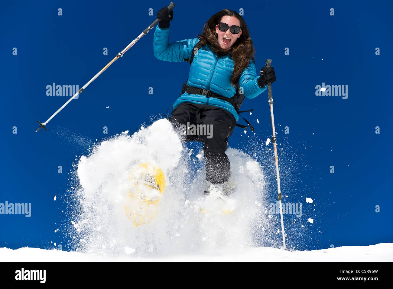 A woman snowshoeing and having fun in fresh powder snow. - Stock Image