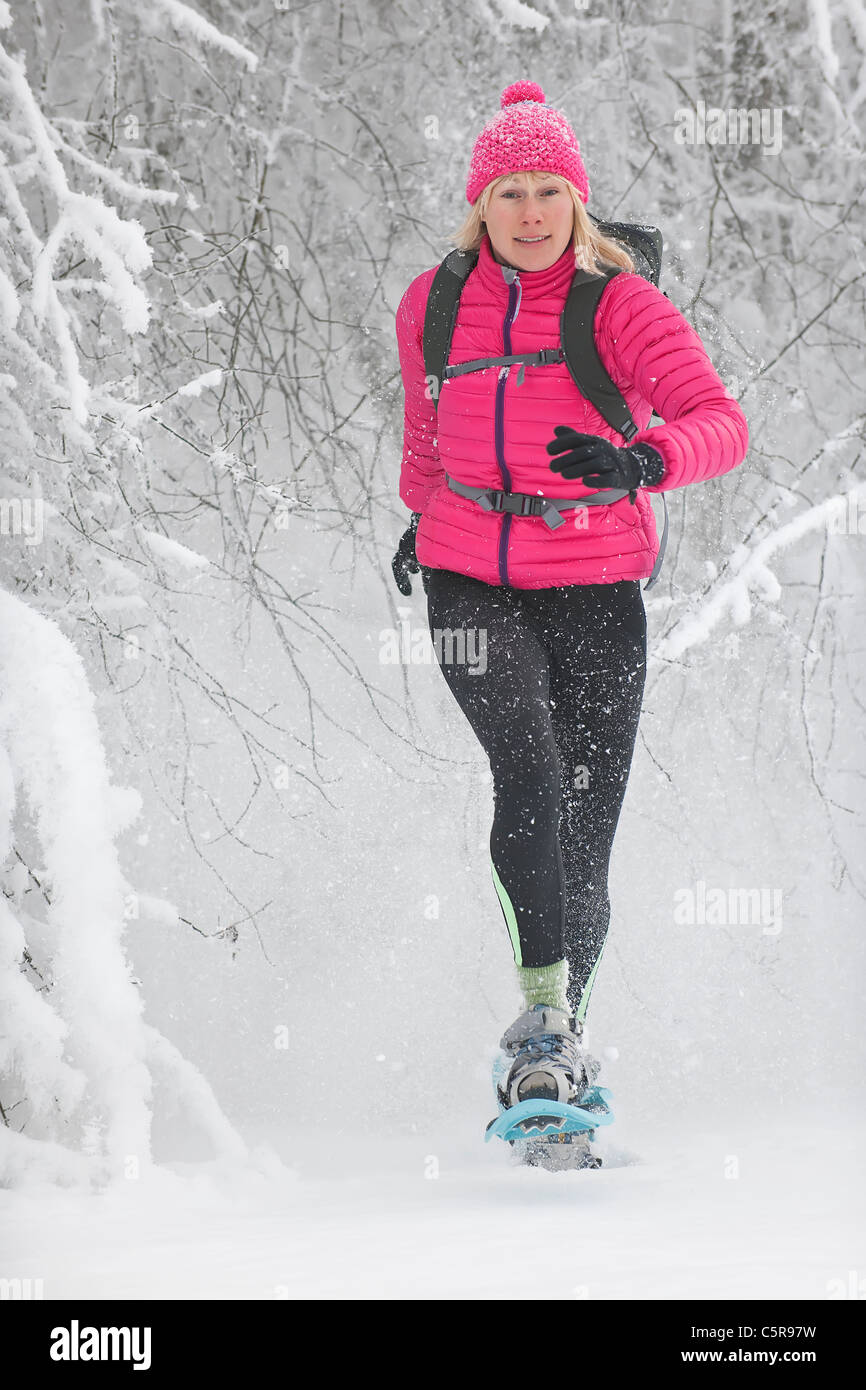 A woman snowshoeing bursts through a snowy trees. - Stock Image