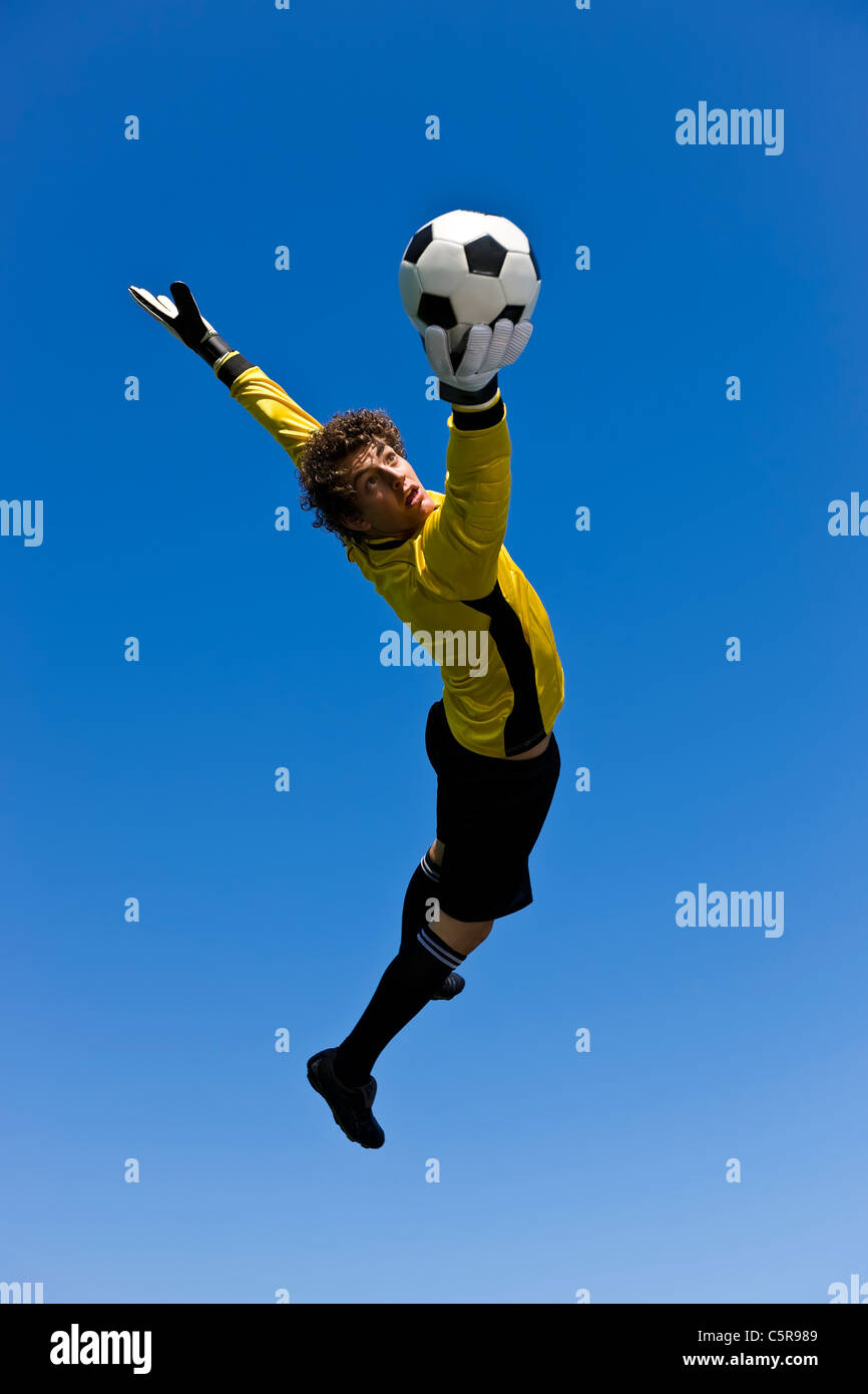 A Goalkeeper succeeds in getting a hand to the ball. - Stock Image
