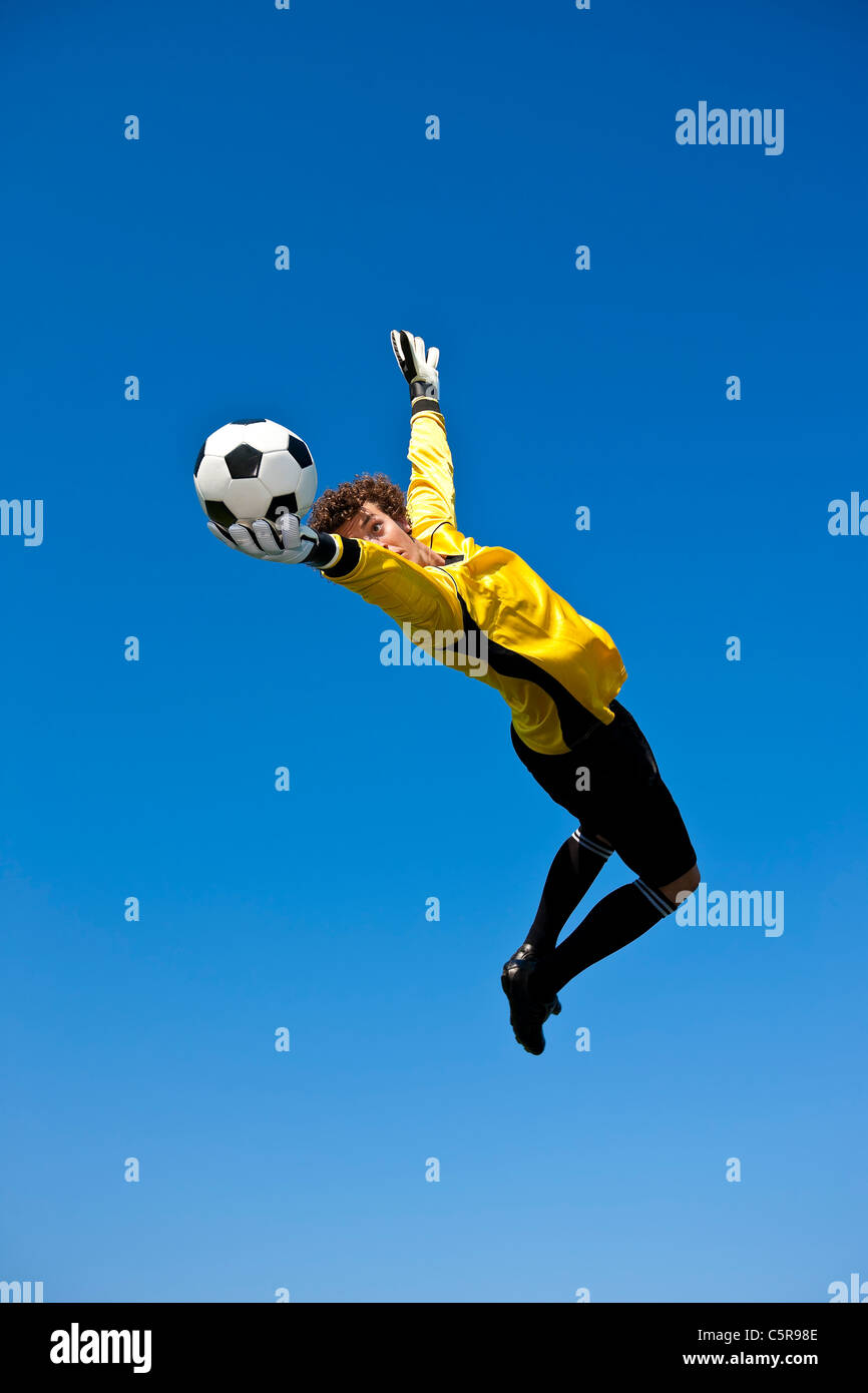 A goalkeeper keeps one eye on the ball and makes the save. - Stock Image