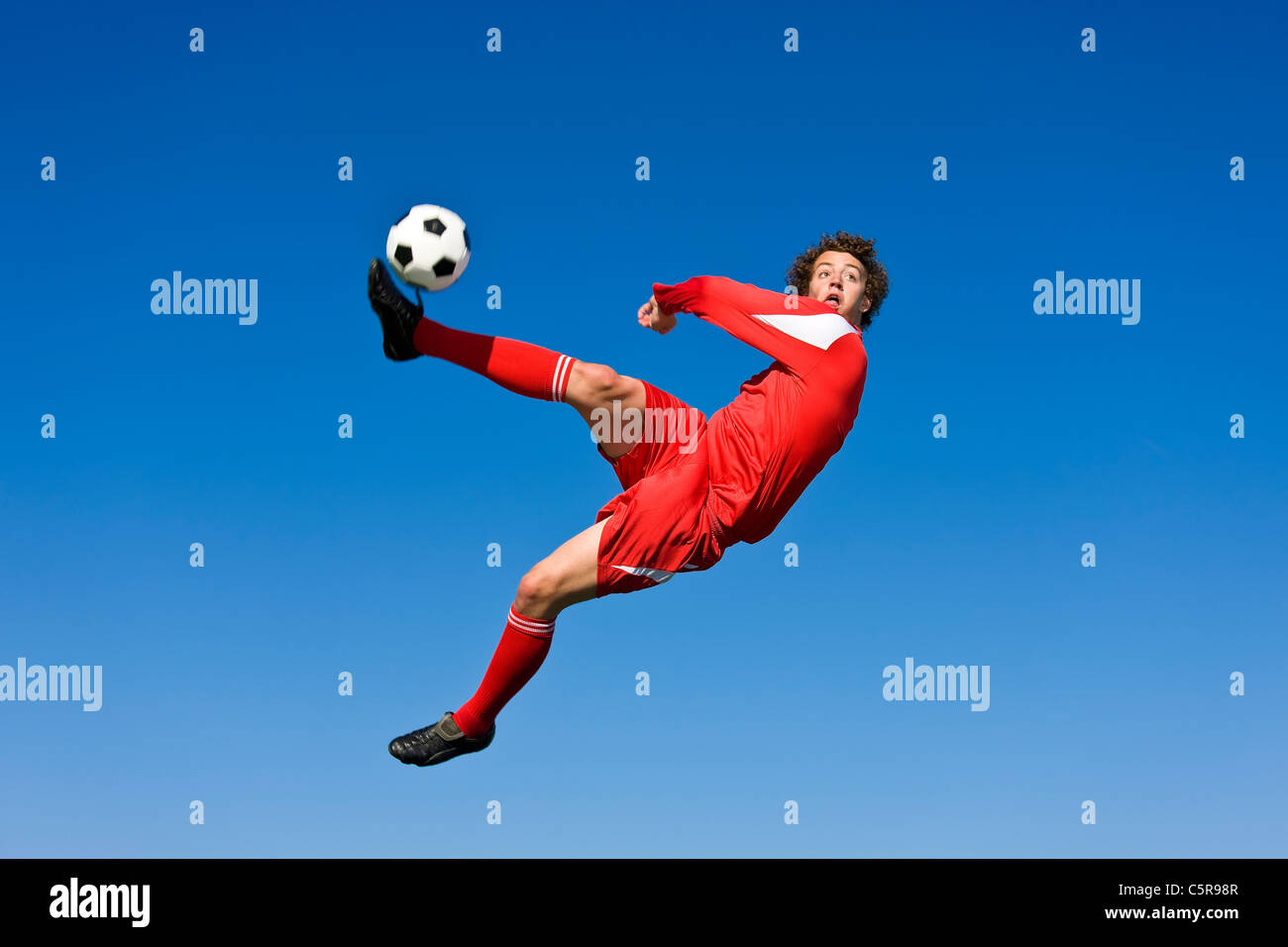 A soccer player volleys the ball. - Stock Image