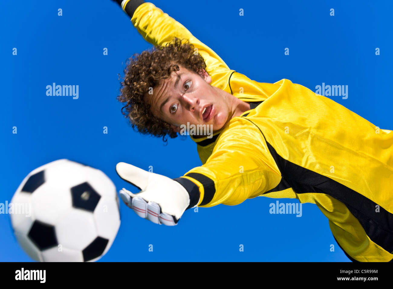A soccer goalie tries to make the save - Stock Image