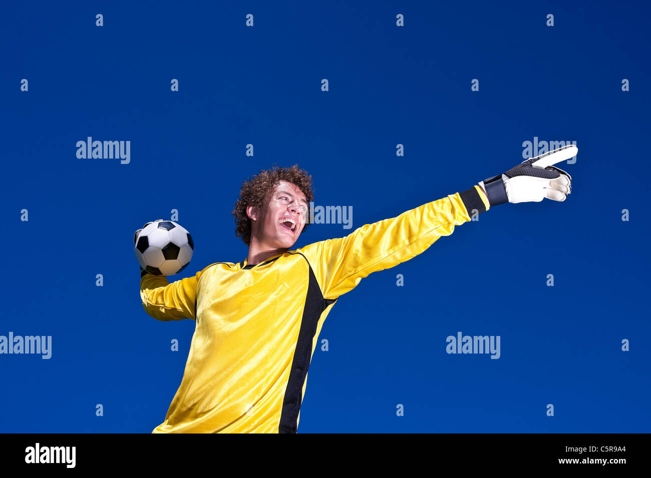 A goalkeeper shouts instruction to team mates - Stock Image
