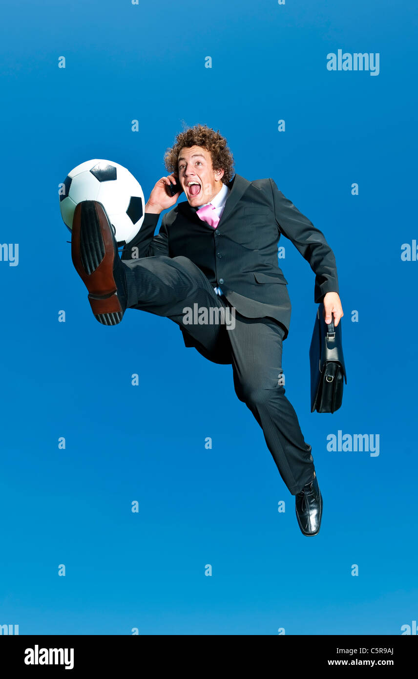 A happy businessman on a cell phone kicks ball. - Stock Image