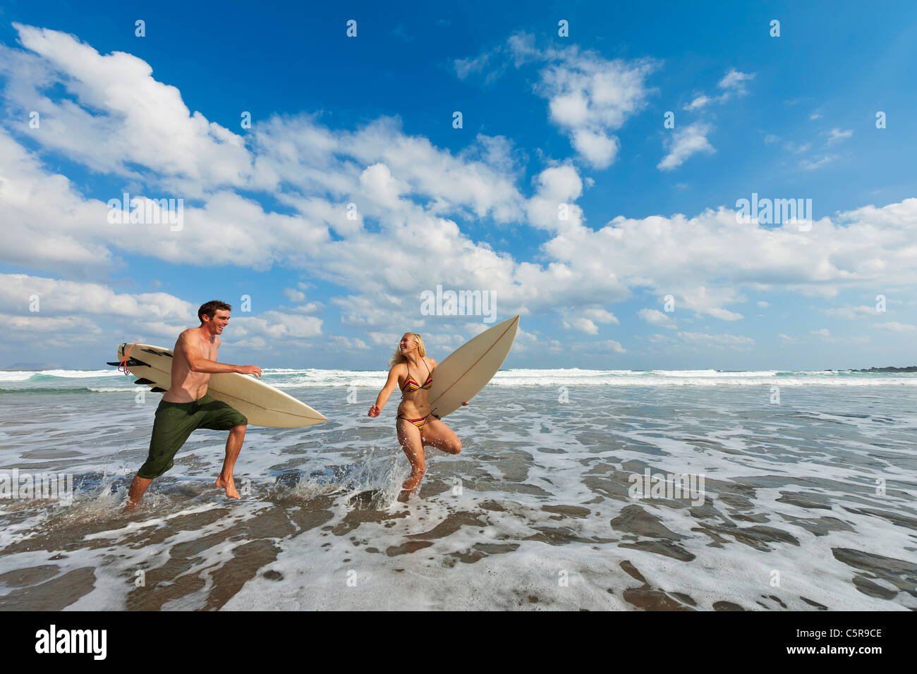 Two surfers having fun running through the surf together. - Stock Image