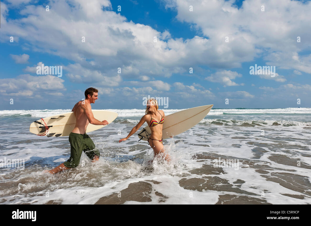 Two surfers having fun in the waves. - Stock Image