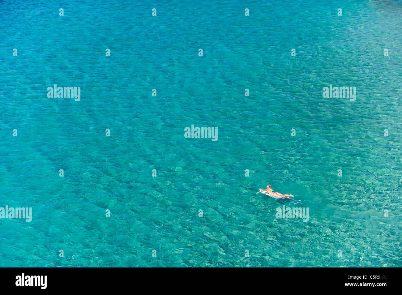 A surfer paddles her board out onto the Ocean. Stock Photo