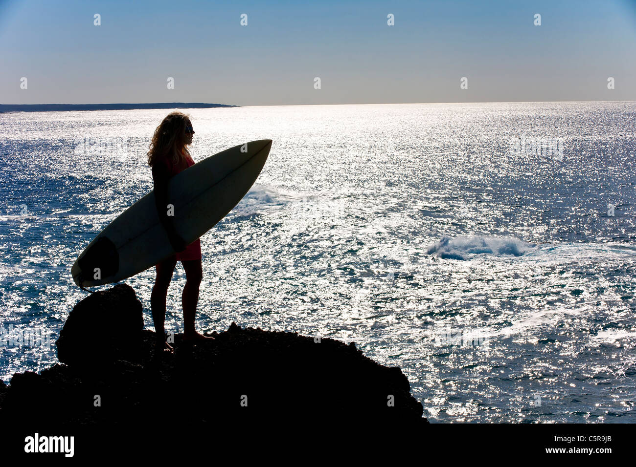 A surfer looks out over the shimmering ocean - Stock Image