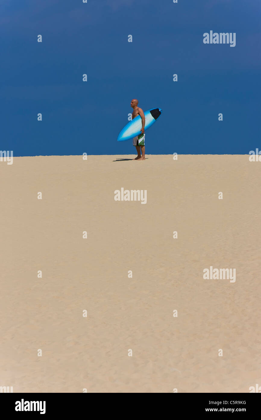 A surfer standing on a sand dune with surfboard. - Stock Image