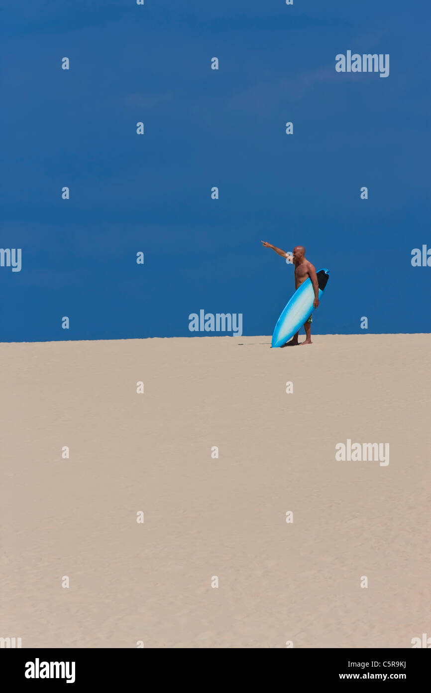 Surfer points out the right direction - Stock Image