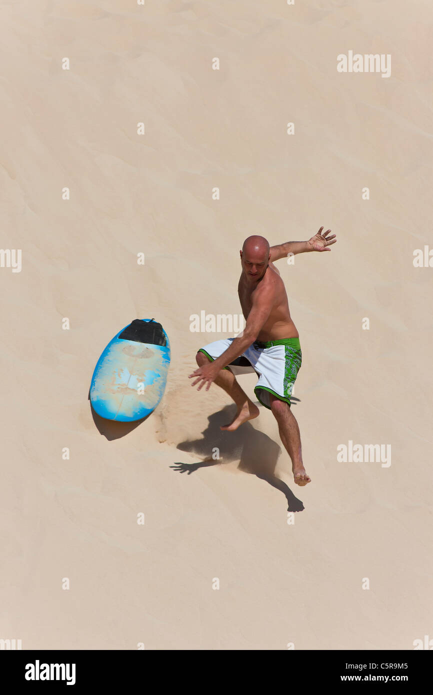 A surfer riding a dune crashes of board. - Stock Image