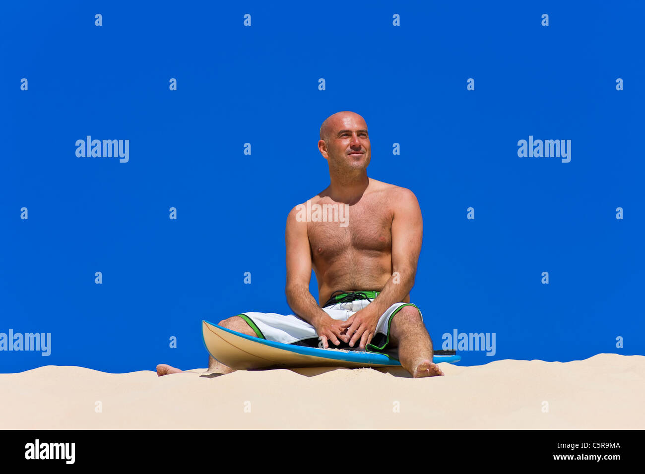 Surfer smiles on board sitting on beach. - Stock Image