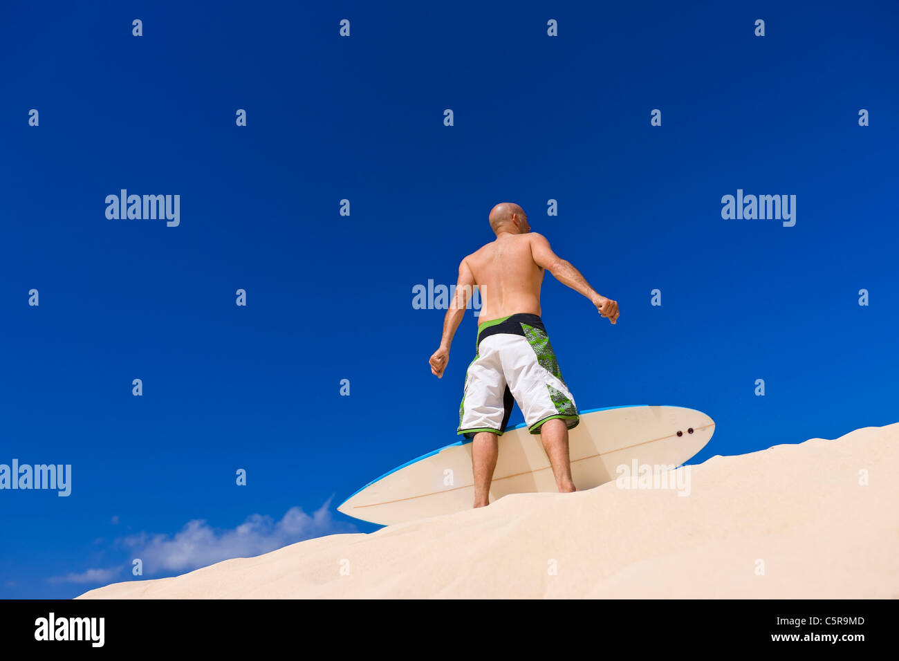 Surfer with board looks out over beach. - Stock Image